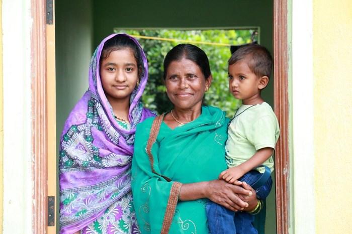 ハビタット・フォー・ヒューマニティらの支援によって建てられたオスマナバード(インド)の家の前に立つマンナビ(45歳)と義理の娘サナと孫のワジード。家は家族に安定とより良い未来への機会を与える。(Habitat for Humanity IndiaRitwik Sawant) ハビタット・フォー・ヒューマニティ